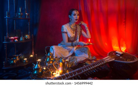 Beautiful young indian woman in traditional Sari clothing and Oriental Jewelry with candle, and the Sitar. Indian bride with festive wedding makeup. Candlelight night in India.