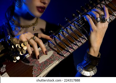 Beautiful young indian woman in traditional clothing with sitar and oriental jewelry. Beautiful bollywood Girl playing the sitar (blue lens effect)