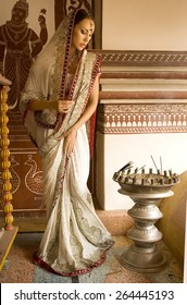 Beautiful young indian woman in traditional clothing with incense, bridal makeup and oriental jewelry. Girl bollywood dancer in Sari, eastern palace. Beautiful princess praying. Eastern fairy tale