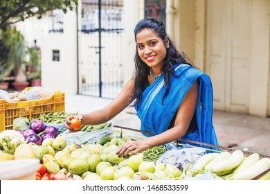 Beautiful young Indian woman wearing saree selecting tomatoes from a vegetable stall in a market