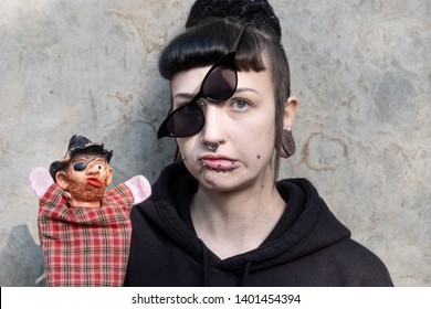 Beautiful young individual, eccentric woman, with interesting hairstyle and piercings and obliquely put on glasses questioningly shows a robber hand puppet.