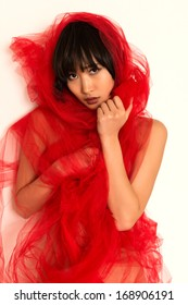 Beautiful young Japanese woman wrapped in red tulle