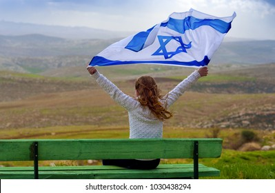 Beautiful young jewish girl sitting and holding  Israel flag.Happy child enjoying great spring landscape: cloudy  sky, field and mountains.Patriotic holiday. Independence day Israel - Yom Ha'atzmaut