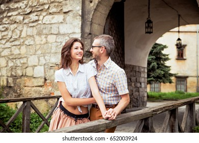 Beautiful young joyful couple in love on the bridge in the old town. Lovers embrace on a wooden bridge. A man and a woman on a walk. Man in glasses and cute brunette woman hugging in the city.