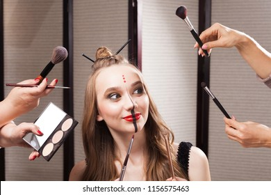 Beautiful young joyful model with professional unusual makeup and a coiffure with topknot and braid made by stylists in a beauty salon is surrounded by hands holding brushes and palette.