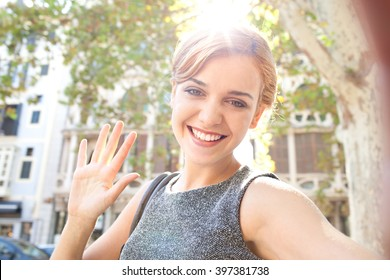 Beautiful young joyful tourist woman sightseeing holiday, holding smart phone to take selfies photos in city, waving at camera outdoors. Portrait of girl using technology, consumer travel lifestyle.