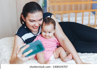 Beautiful young Kazakh mother is making selfie with her adorable little baby and smiling while sitting on sofa at home