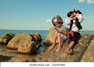Beautiful young kids pirate boy and girl holding a pirate map and a magnifying glass looking for buried treasure on the beach