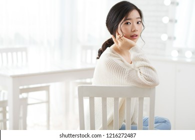 Beautiful young Korean woman sitting in white room and turning back to camera