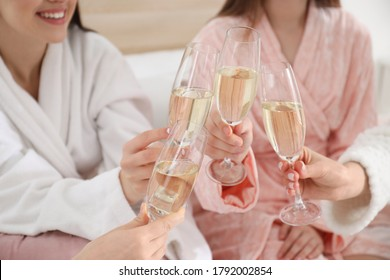 Beautiful young ladies clinking glasses of champagne at pamper party, closeup. Women's Day