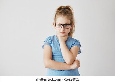 Beautiful young lady with bright blue eyes and light hair posing in glasses with hand under her chin and serious face expression.