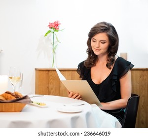 Beautiful young lady choosing food in restaurant