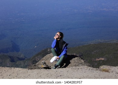 Beautiful young lady climbed on the mountain, sitting on the edge, happy and smiling. Sunglases on her face, long blonde hair.Wearing warm jacket and pants. Impressive view from the top of mountain