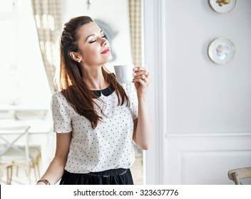 Beautiful young lady with coffee cup