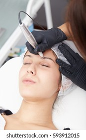 beautiful young lady getting tattoo. professional tattooist making eyebrow make up