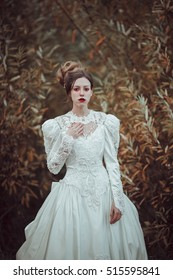 Beautiful young lady in gorgeous vintage white dress standing in the garden. Wedding fashion. Waiting concept. Melancholy
