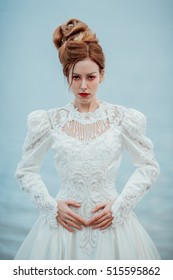 Beautiful young lady in gorgeous vintage white dress at the seaside. Wedding fashion. Waiting concept. Melancholy