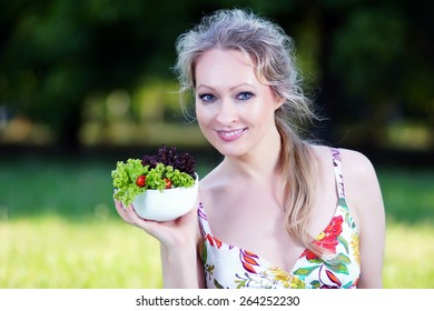 Beautiful young lady hold fresh salad in green field and smile into camera.