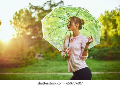 Beautiful young lady holding multicolored umbrella. Blue sky outdoors. Happy girl on countryside landscape