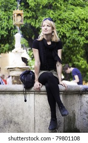 Beautiful young lady sitting at the edge of the fountain at the main square in Cordoba, Spain, on a sunny day.