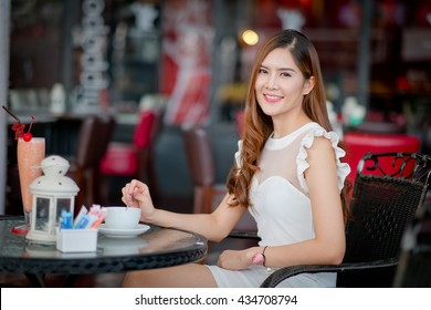 Beautiful young lady  sitting at the summer terrace and drinking coffee