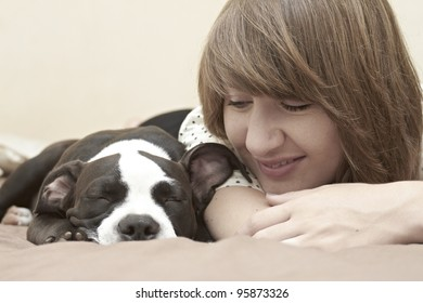 Beautiful young lady smiling at her Pit Bull puppy asleep on bed