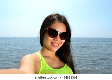 Beautiful young lady taking selfie on the beach