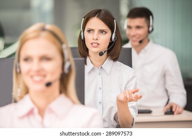 Beautiful young lady talking on headset at call center office.