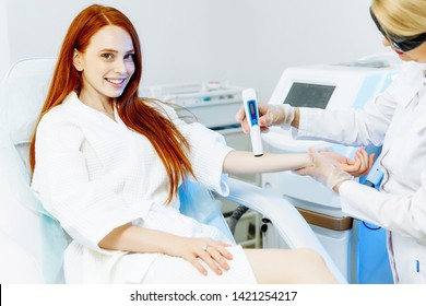 Beautiful young lady in white bathrobe lying on daybed while aesthetician in sterile gloves preparing her skin for laser epilation skin type measurement