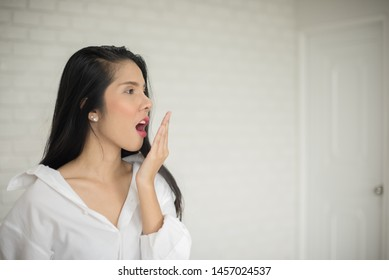 Beautiful young lady with white shirt in white room, Asian young woman covering her mouth by hand, Disgust and bad smell, Bad breath, Bad smell air from a mouth. Oral hygiene concept-Image