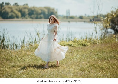 Beautiful young lady in white vintage dress walking near the river in the sun.