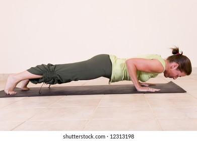Beautiful young lady in the yoga 'Four limbed staff pose - Chaturanga Dandasana'.