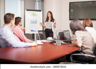 Beautiful young Latin brunette giving a business presentation to some of her clients in a meeting room
