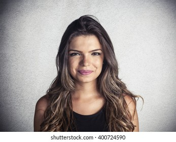 Beautiful young latin girl smiling on a wall background