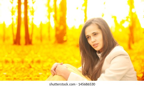 beautiful young latin hispanic woman speking on mobile phone in yellow autumn park  Copy space for inscription