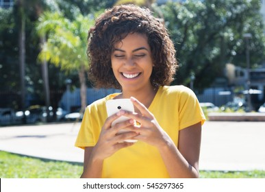 Beautiful young latin woman messaging by phone