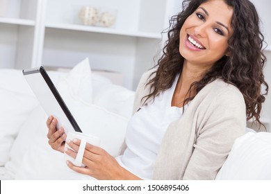 Beautiful young Latina Hispanic woman smiling, relaxing and drinking a cup of coffee or tea at home using tablet computer for social media
