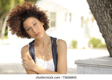 Beautiful young Latino woman sitting under the shade of a tree on sunny day.