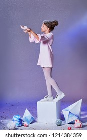 Beautiful young little child in elegance pink dress for party standing on a cube, catches snow by hand. Holidays, christmas, new year, x-mas, Fashion concept. Studio, purple background.