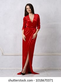 Beautiful young long haired brunette woman dressed in stylish long pale red velvet dress with high split standing against white wall on background. Elegant female model wearing evening outfit.