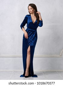 Beautiful young long haired brunette woman dressed in stylish long pale blue velvet dress with high split standing against white wall on background. Elegant female model wearing evening outfit.