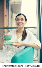 Beautiful young long haired woman looking glad and smiling while sitting in the armchair with a cup of tea