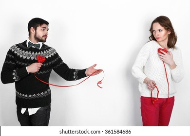 Beautiful young love couple in warm knitted pullovers celebrating Valentine's Day, performing funny emotional scenes with festive decorations in the form of hearts