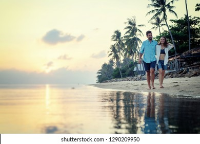 Beautiful young love happy couple walking arm in arm on the beach at sunset during the honeymoon vacation travel,