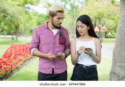 Beautiful and young lover enjoy their smart phone and sitting on the bench together, Lover enjoy their smart phone with happiness feeling, Age 20-30 years.