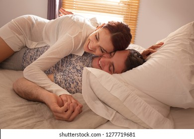 Beautiful young lovers couple laying together on bed laughing happy and playful, sensual romance, passion and desire, home interior. Boyfriend and girlfriend games in bedroom, relationships lifestyle.