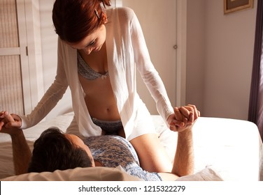 Beautiful young lovers couple sexually playful together on bed, closeness romance, passion and desire, home interior. Sensuality in bedroom, flirting experimenting fun lifestyle.