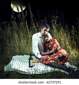 Beautiful young lovers in the moonlight picnic