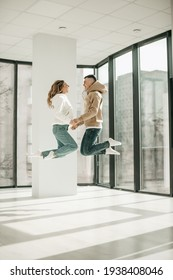 Beautiful young lovers pair of man and women in white and beige hoodies blue jeans hugging, jumping at home. Girl blonde, happy people, romance, date, fun, white interior, passion, relationship.