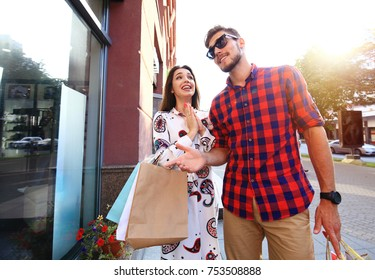 Beautiful young loving couple carrying shopping bags and enjoying together. Consumerism concept.